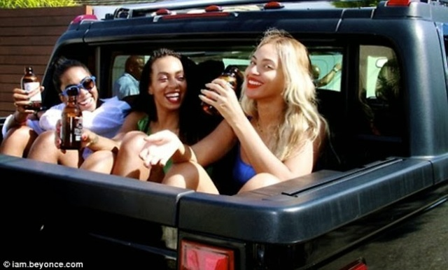 Beyonce (right), a friend (left) and her sister and fellow singer/songwriter Solange Knowles enjoy a ride - Red Stripe beers in hand - on vacation in Portland, Jamaica last year.